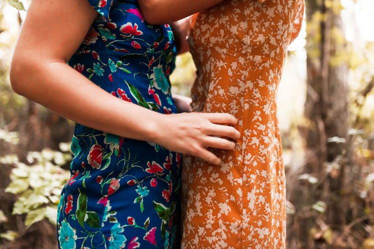Midsection of lesbians standing outdoors