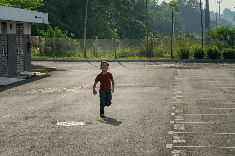 Full length of boy on road against trees