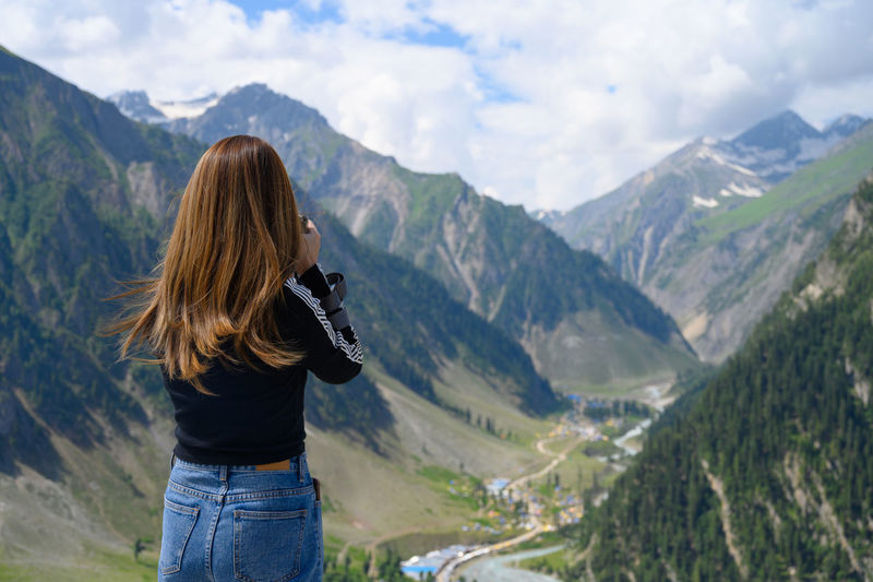 Rear view of woman in mountains against sky