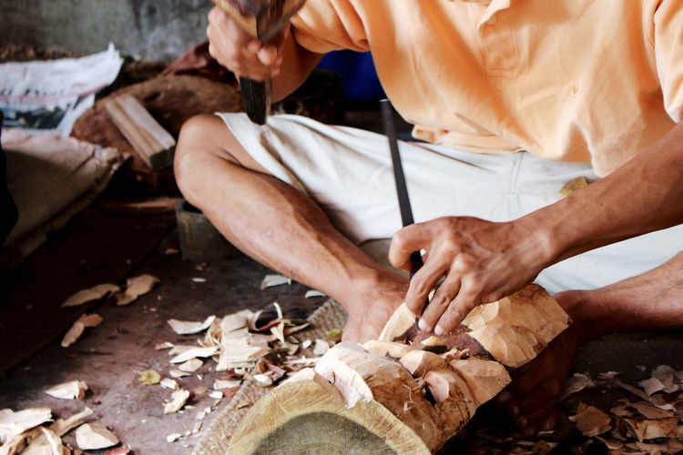 One Person Real People Holding Men Occupation Midsection Working Food Human Hand Focus On Foreground Day Preparing Food Preparation  Sitting Hand Food And Drink Adult Wood - Material Nature No Face Hammer Carpentry Sculpture Timber Chisel Craftsmanship