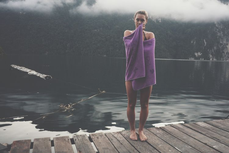 Portrait of beautiful woman wrapped in purple towel against lake during foggy weather