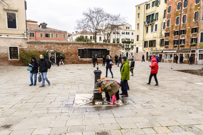 Old woman drinking from a water fountain on the street in Campo del Ghetto, Venice, Italy. Adult Architecture Building Exterior Day Drinking Water Full Length Outdoors People Woman Young Adult