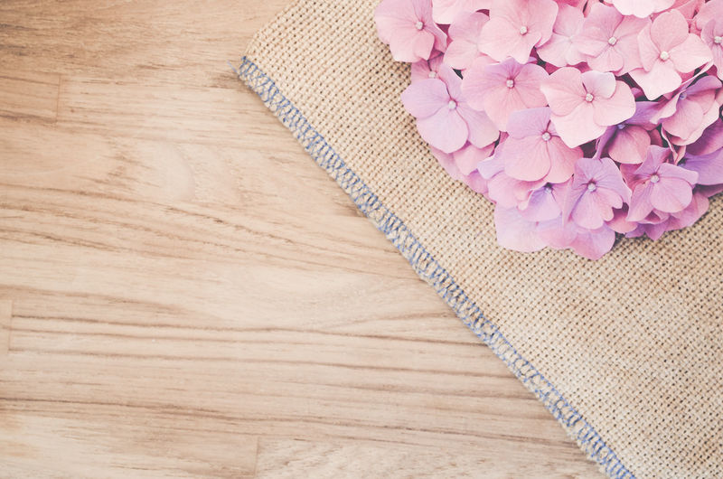 High Angle View Of Pink Hydrangeas On Place Mat Over Wooden Table