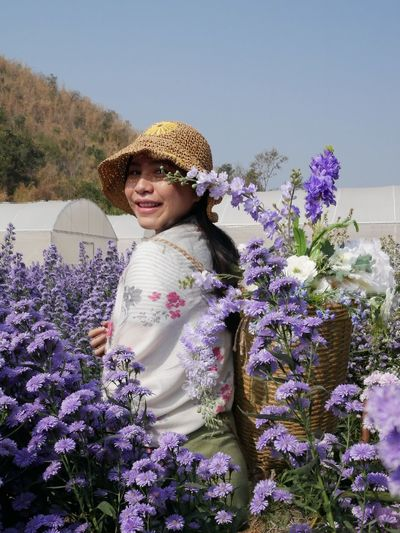Portrait of smiling woman with purple flowering plants
