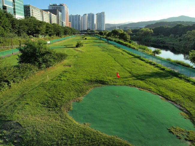 Architecture City City Lights Field Golf Course View Grass Green Color Landscape Nature Outdoors Red Flag Sky Urbanphotography Water