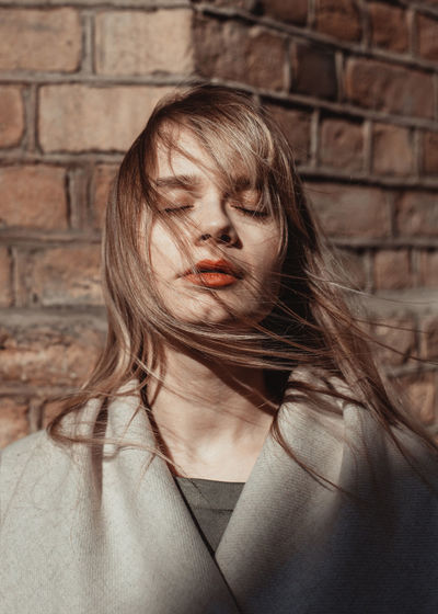 Portrait of young woman against wall. hair and wind
