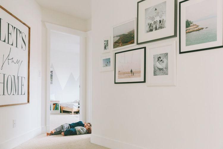 Siblings lying in corridor at home