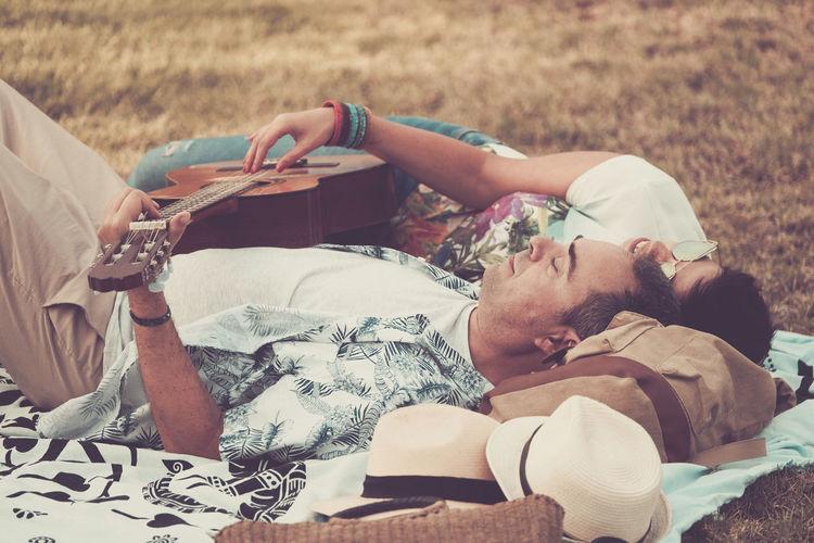 Couple with guitar lying on blanket