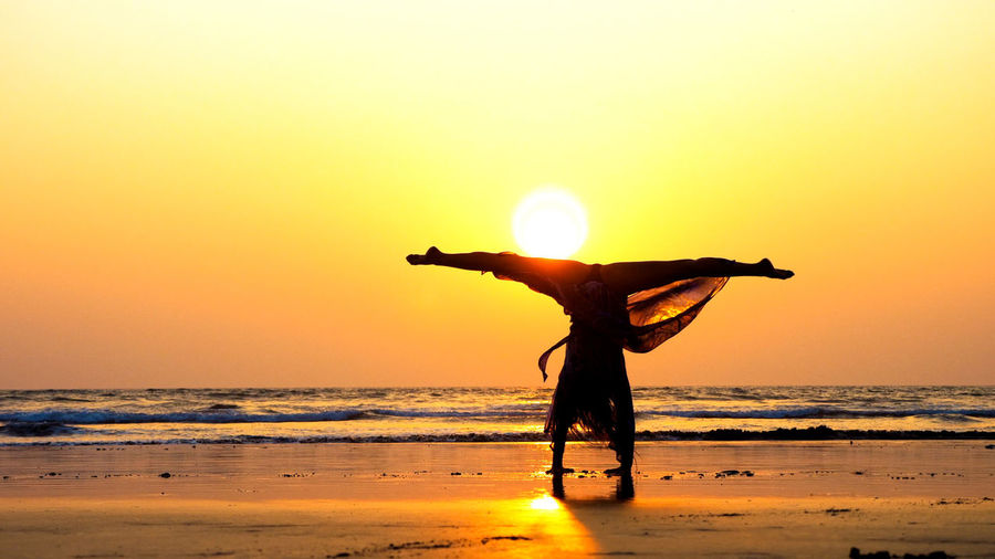 Silhouette woman practicing handstand at beach during sunset