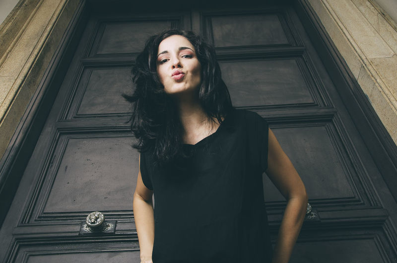 Portrait Of Beautiful Woman Puckering Lips Against Closed Wooden Door