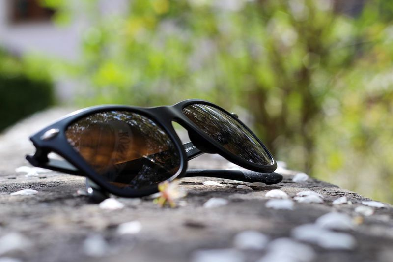 Close-up of sunglasses on rock