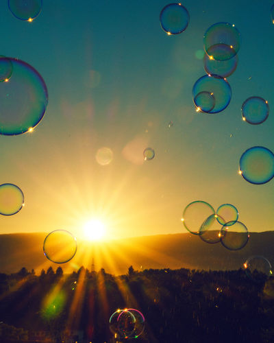 Close-up of bubbles against rainbow in sky