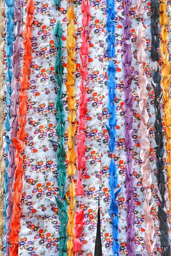 Colorful paper cranes hanging by wall during traditional festival