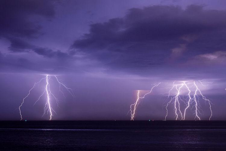 Firework display over sea against dramatic sky