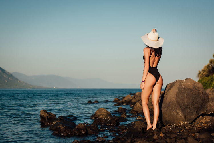 Beauty In Nature Clothing Hat Land Leisure Activity Lifestyles Mountain Nature One Person Outdoors Real People Rock Rock - Object Scenics - Nature Sea Sky Solid Sun Hat Tranquil Scene Tranquility Water