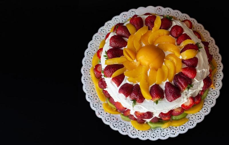 High angle view of cake on plate against black background