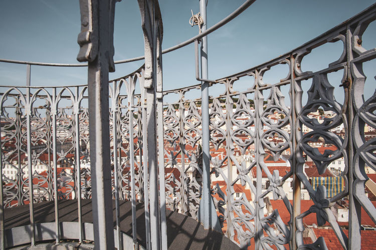 Low angle view of railing by building against sky