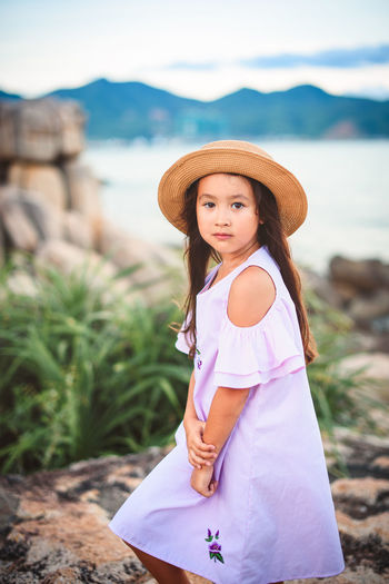 Portrait of girl wearing hat while standing at lakeshore