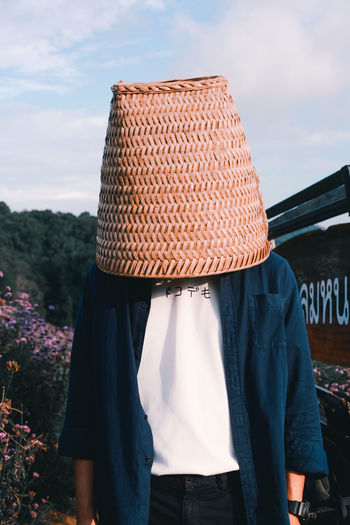 Man covering head with basket standing in backyard