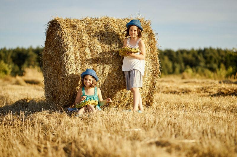 Siblings standing on field
