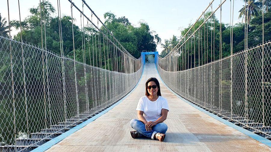 Full length of woman sitting on footbridge