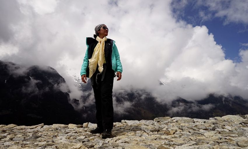 Low Angle View Of Woman Standing On Mountain Against Cloudy Sky