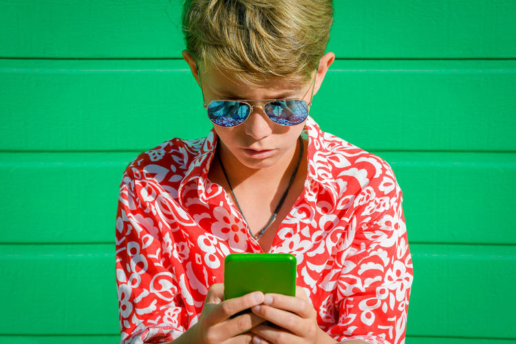 Beautiful blond child with serious expression using cellphone on green background, mirror sunglasses, white red flowered vintage shirt Portrait of trendy boy Young male awaits his late girlfriend One Person Front View Holding Women Real People Green Color Lifestyles Casual Clothing Red Portrait Young Adult Leisure Activity Looking Headshot Glasses Child Wireless Technology Childhood Outdoors Innocence Turquoise Colored