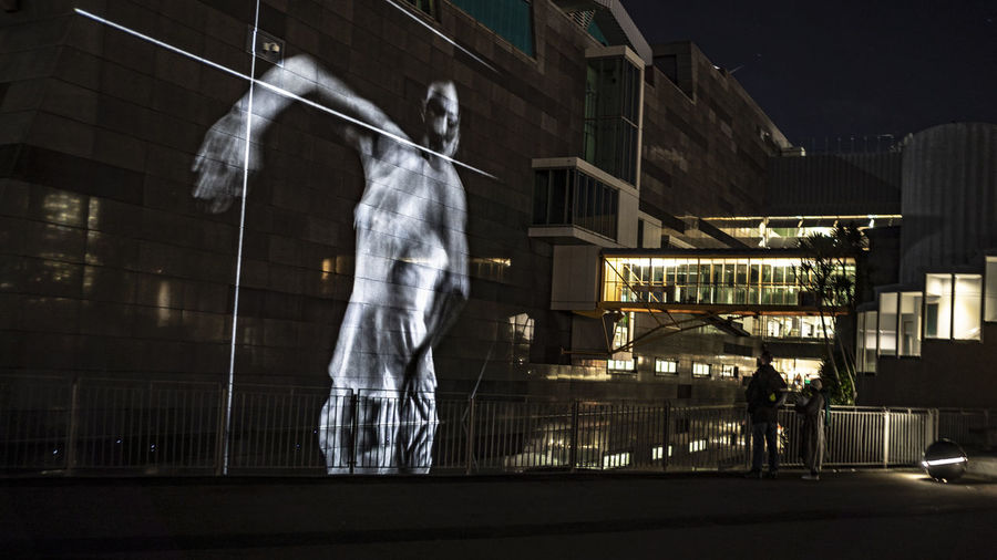 Aotearoa Adult Architecture Building Building Exterior Built Structure City Dancer Glass - Material Illuminated Light Motion Night People Performance Performance Art Projection Real People Standing Street Transparent Two People Unrecognizable Person