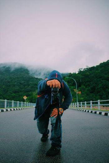 Man photographing on road against sky