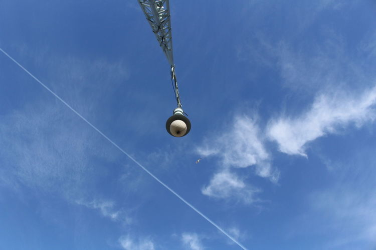 Low angle view of crane against vapor trail in sky