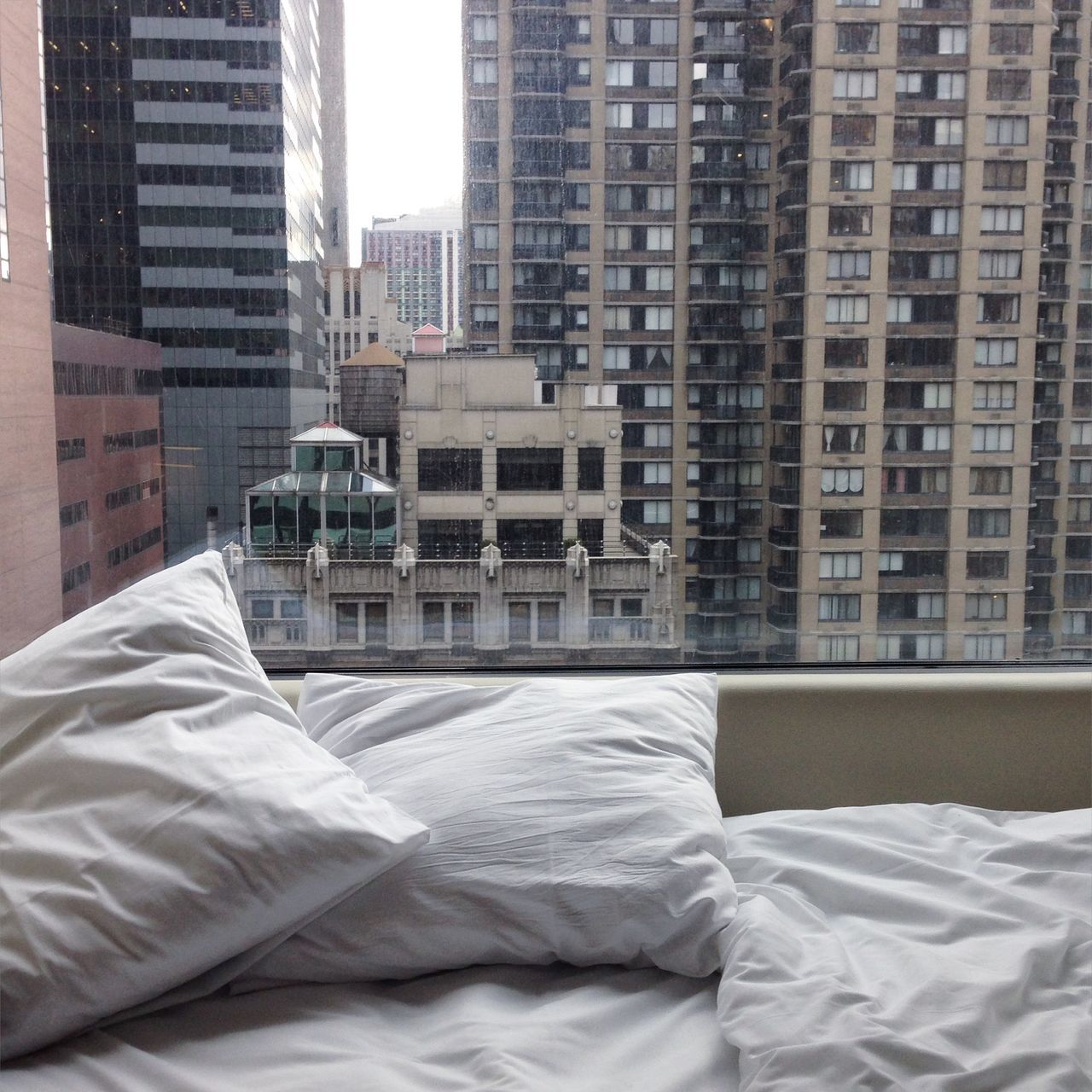 Bed and cushion by window with buildings in background