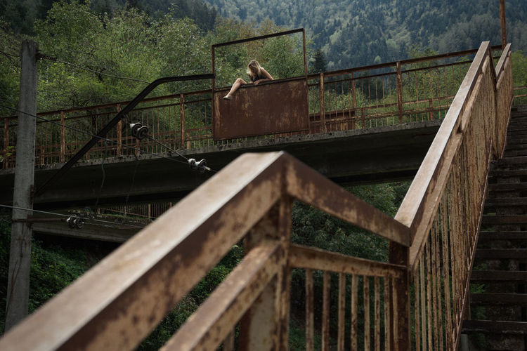 Low angle view of woman committing suicide on bridge