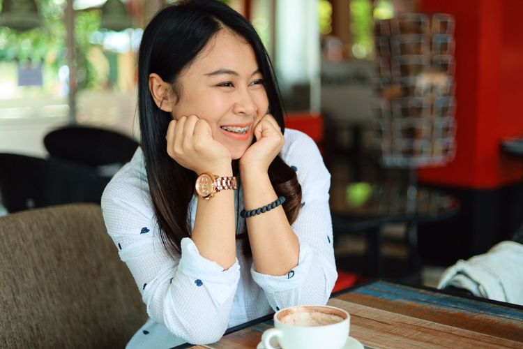 Sitting One Person Young Adult Women Food And Drink Young Women Smiling Adult Happiness Leisure Activity Table Real People Lifestyles Drink Casual Clothing Indoors  Focus On Foreground Restaurant Front View Hair Beautiful Woman Hairstyle