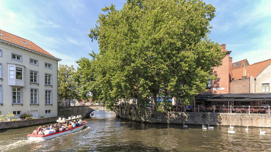 Bruges, Belgium - July 7, 2017: Tourists on a boat in one of the numerous canals of Bruges, Flanders in Belgium Beer Belgium Brugge Chocolate Dijver Canal Duvel Flanders Panoramic View Provinciaal Hof West Flanders Aerial View Belfry Tower Bikes Bruges Europe Flower French Fries Holland Market Square Medieval Town Mussels