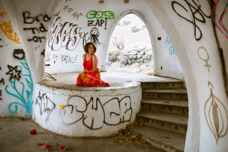 Portrait of young woman sitting on floor in graffiti