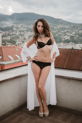 Portrait Of Woman Standing In Lingerie On Terrace