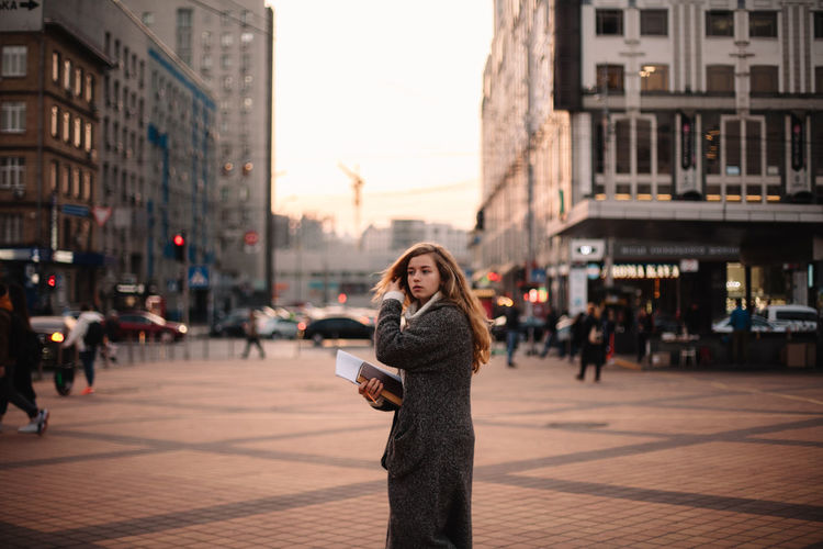 Woman standing on street with city in background