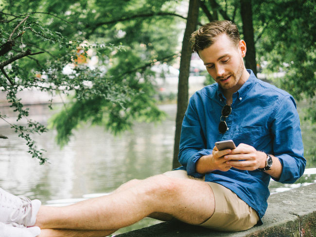 natural sitting position! Adult Adults Only Casual Clothing Communication Day Holding Lifestyles Looking Men Mobile Phone One Man Only One Person One Young Man Only Only Men Outdoors People Portable Information Device Real People Sitting Smart Phone Technology Text Messaging Wireless Technology Young Adult Young Men