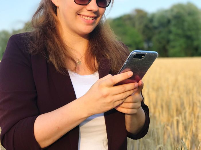 Midsection of smiling woman using mobile phone