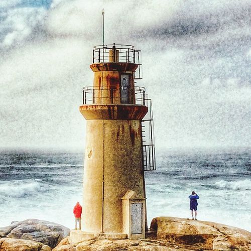 muxia men people atlantic water sea two tourism rocks lighthouse galicia spain waves powerful photography