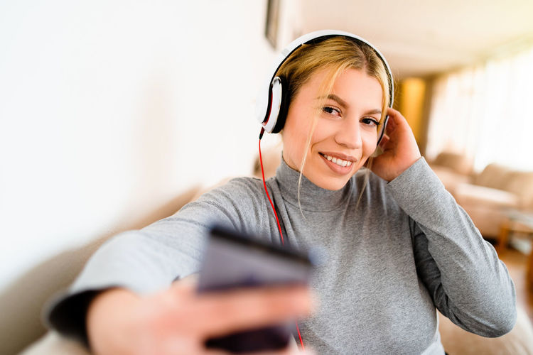 Technology Communication Smiling Wireless Technology Listening Headphones Happiness Connection Music One Person Mobile Phone Holding Indoors  Front View Lifestyles Young Adult Portrait Using Phone Telephone