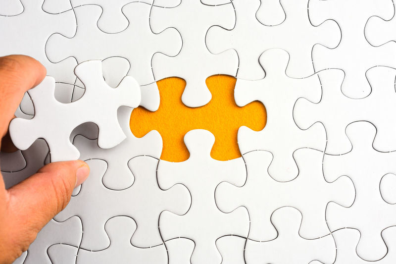 Cropped Hand Holding Jigsaw Puzzle