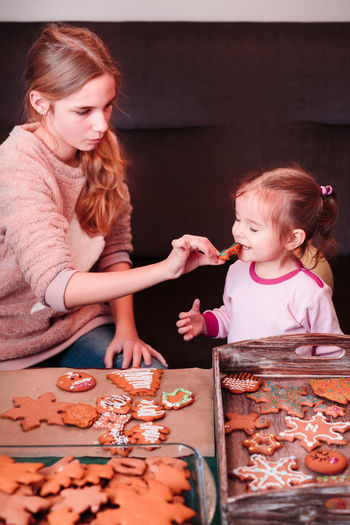 Girl Feeding Sister With Cookies