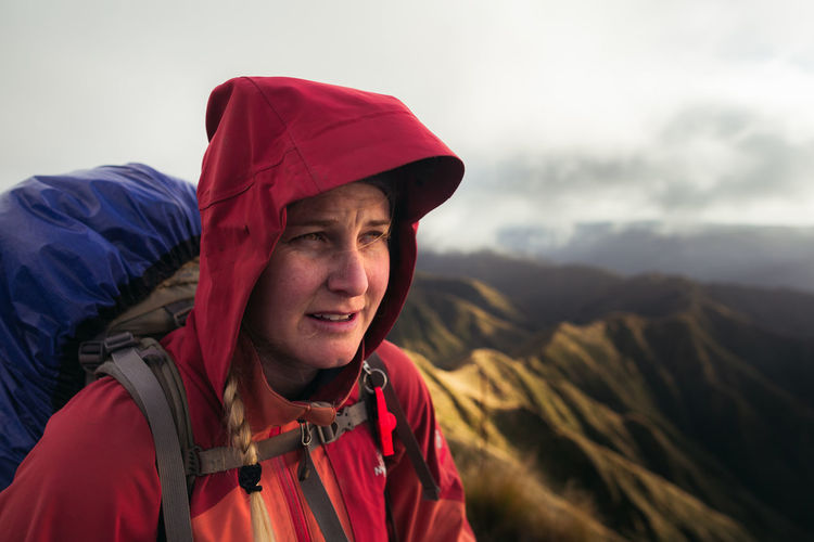 Woman with backpack looking away while standing on mountain