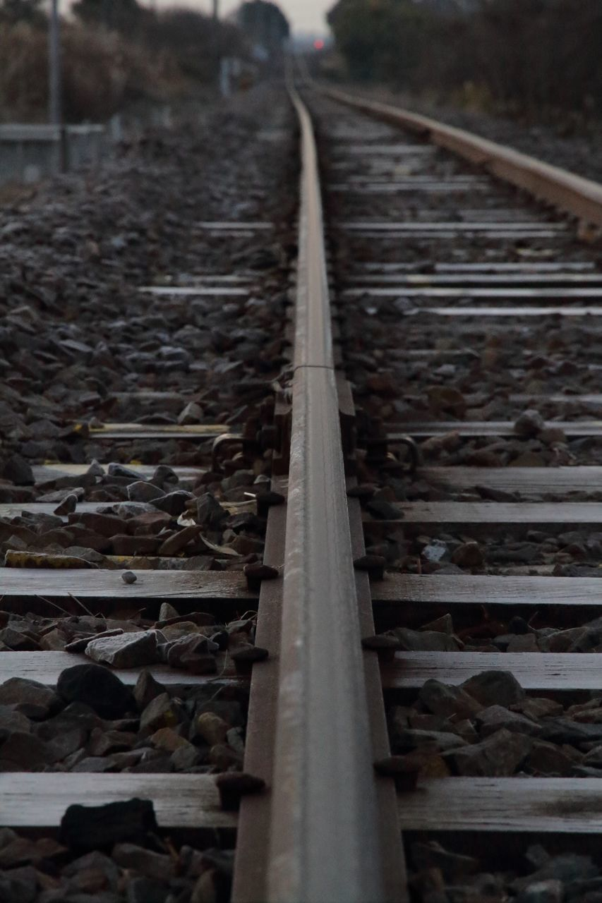 rail transportation, track, railroad track, metal, transportation, direction, no people, the way forward, day, diminishing perspective, nature, vanishing point, outdoors, public transportation, surface level, connection, focus on foreground, railroad tie, close-up, mode of transportation, straight, gravel, long