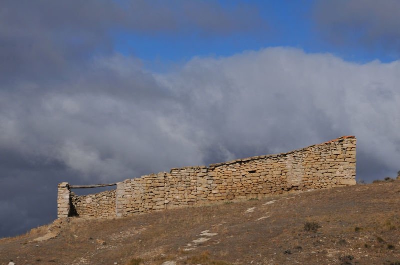 Low angle view of fort against cloudy sky