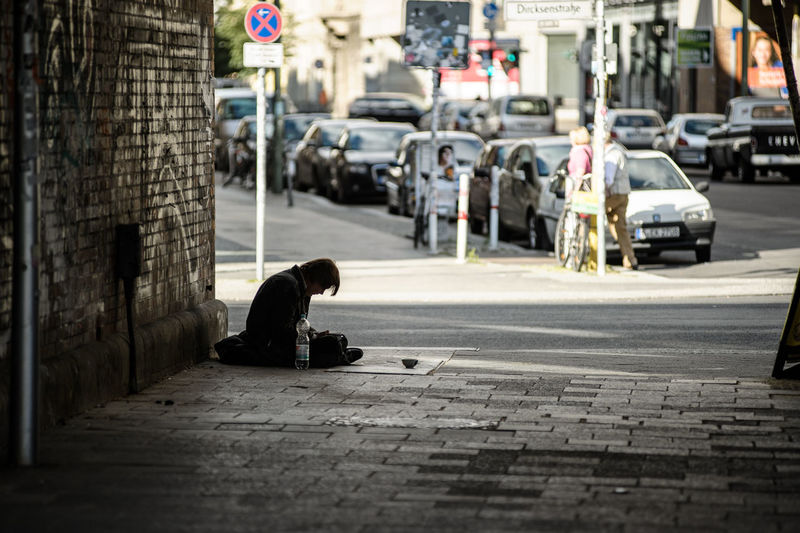 Side view of beggar sitting on city street