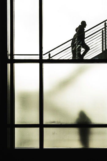 Silhouette man walking on bridge