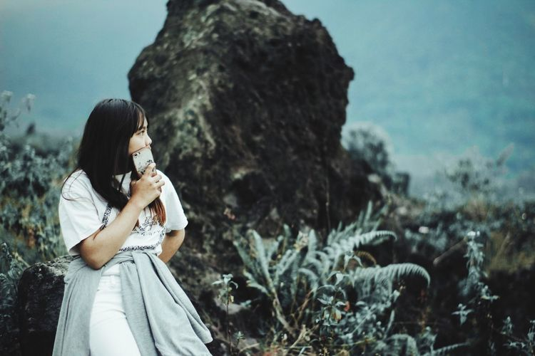 Young woman looking away while leaning on rock
