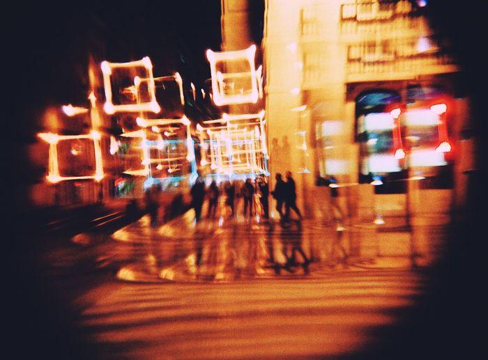 People walking on illuminated street against buildings at night